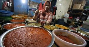 Seorang pedagang mengaduk bumbu masak yang dijual Rp 10 ribu per kg di pasar tradisional Pusat Pasar Medan, Sumut, Jumat (11/10).