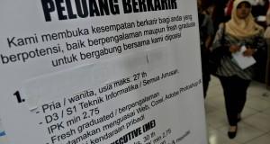 Pencari kerja melintas di dekat sebuah poster salah satu stan perusahaan, saat berlangsungnya Bursa Kerja di Semarang, Jateng, Rabu (9/10).