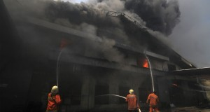 Petugas berusaha memadamkan api saat terjadi kebakaran di sebuah gudang ban, Pluit, Jakarta Utara, Senin (14/10)