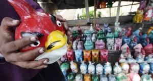 Penjual memegang sebuah celengan yang dijual di Juru Mudi, Tangerang, Banten, Senin (21/10).