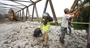 Pekerja memeperbaiki jembatan pintu air 10 di Tangerang, Banten