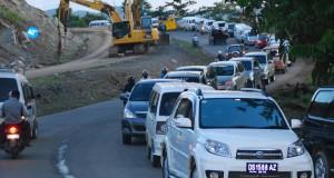 Sejumlah kendaraan berjalan tersendat ketika sebuah alat berat digunakan untuk pelebaran jalan di wilayah Distrik Sentani Timur, Kabupaten Jayapura, Papua (12/10)