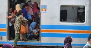 Seorang penumpang duduk di lantai KRL meskipun kondisi kereta  penuh  di stasiun Manggarai