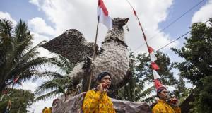 Masyarakat dengan pakaian adat Jawa dan memanggul atribut burung raksasa mengikuti kirab budaya Rasulan di kawasan Gunung Api Purba, Nglanggeran, Gunung Kidul, Yogyakarta, Minggu (13/10).