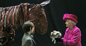Britain's Queen Elizabeth receives flowers from an actor during a visit to the National Theatre in London