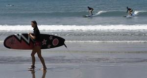 Sejumlah wisatawan berlatih surfing di Pantai Kuta, Bali, Senin (11/11).