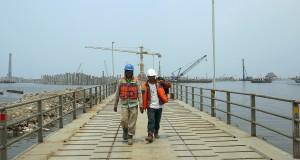 Dua pekerja berjalan di atas jembatan sementara (temporary bridge) dengan latar belakang pembangunan Terminal Peti Kemas Kalibaru, di Pelabuhan Tanjung Priok, Jakarta, Kamis (7/11).