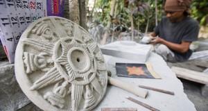 Seorang perajin membuat ornamen bangunan lambang Kerajaan Majapahit, Surya Majapahit, dari bahan batu di Jati Sumber, Trowulan, Kabupaten Mojokerto, Jawa Timur, Jumat (8/11)