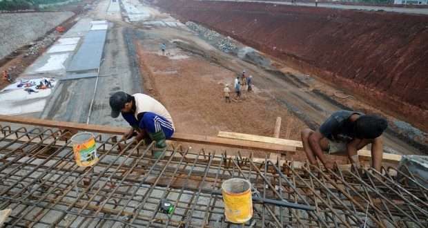 Pekerja menyelesaikan pembangunan jalan tol Cijago tahap II di Depok