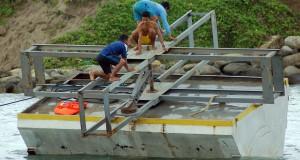 Relawan melakukan uji coba Pembangkit Listrik Tenaga Gelombang Laut - Sistem Bandulan (PLTGL-SB), di Muara Penjalinan, Padang, Sumbar,