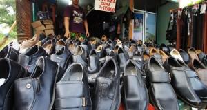 Penjual merapihkan sepatu di toko sepatu di kawasan Cipete, Tangerang, Banten