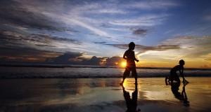 Dua anak bermain pasir saat matahari terbenam (sunset) di Pantai Ketaping, Piaman, Kab.Padangpariaman, Sumbar, Minggu (24/11)