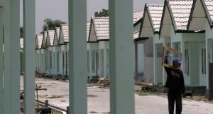 Seorang pekerja memanggul sebuah bingkai jendela di sebuah proyek pembangunan rumah sederhana sehat (RSH) di Kediri, Jawa Timur