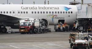 Petugas bagasi menaikan barang ketika menyiapkan penerbangan maskapai Garuda Indonesia di Terminal 2 Bandara Soekarno-Hatta Tangerang, Banten, Selasa (17/12).