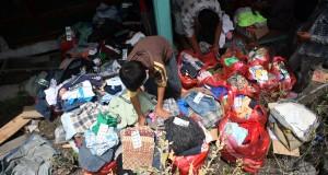 Seorang relawan menata pakaian hasil sumbangan  masyarakat di posko relawan Laharpang, Puncu, Kediri,