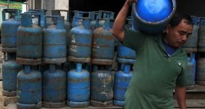 Pekerja memikul tabung gas elpiji ukuran 12 Kg di gudang pengecer di Kebonjahe, Serang, Banten, Minggu (12/1).