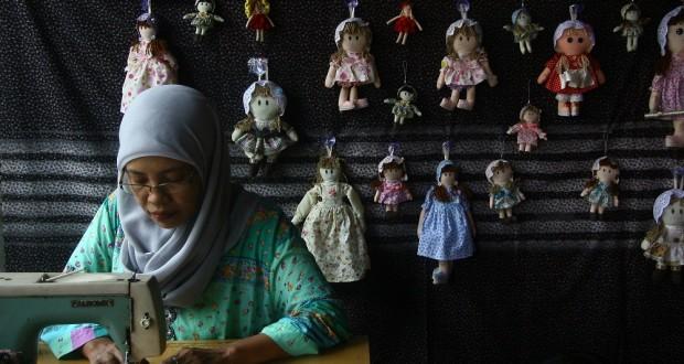 Perajin menyelesaikan pembuatan boneka country berbahan kain di sebuah industri rumahan di Tanggulangin, Sidoarjo, Jatim, Senin (11/2).