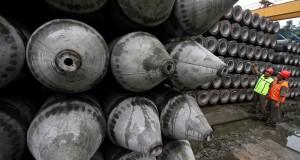 Pekerja memeriksa kondisi dan menghitung jumlah beton paku bumi di Pabrik Wika Beton, Cileungsi, Bogor, Jawa Barat
