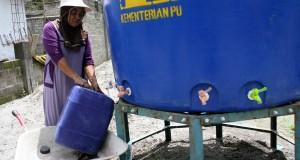 Seorang warga mengambil air menggunakan jerigen di tandon air yang di sediakan Kementrian PU di Desa Kebonrejo, Kepung, Kediri, jawa Timur. Sabtu (1/3). Ratusan Kepala Keluarga (KK) dikawasan terdampak