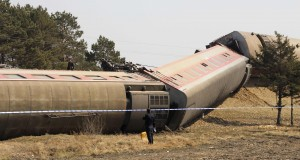 A police officer stands next to a derailed passenger train in Hailun county