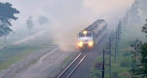 Kereta api menembus asap tebal yang menutup jalur kereta api di Kota Madiun, Ja