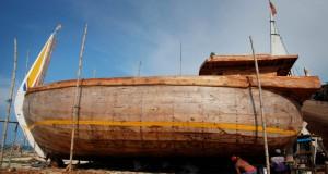Pekerja melakukan pekerjaan akhir pada pembuatan kapal kayu di galangan kapal kawasan Sarang, Rembang, Jateng, Kamis (1/5)