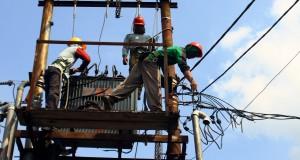 Pekerja memasang trafo penurun tegangan di kawasan pertokoan Tidar, Malang, Jawa Timu