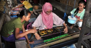 Dua orang anak suku Sasak membantu wisatawan yang tengah mencoba menenun kain Songket di Desa Sukarara, Jonggat, Lombok Tengah, Nusa Tenggara Barat (NTB), NTB, Sabtu (14/6).