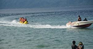 Sejumlah wisatawan melakukan rekreasi air dengan banana boat di obyek wisata pantai pasir putih Tanjung Karang, Kabupaten Donggala, Sulawesi Tengah, Sabtu (21/6).