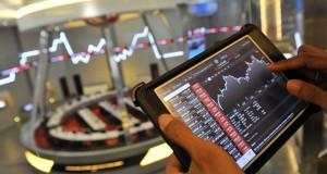 Seorang jurnalis mengamati pergerakan Indeks Harga Saham Gabungan (IHSG) di Bursa Efek Indonesia, Jakarta,