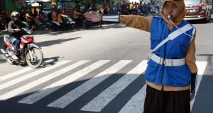 Seorang pelajar SMA mengatur lalu lintas di Jalan raya Ahmad Yani, Kota Kediri, Jawa Timur, Jumat (22/8)