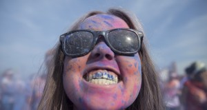 A woman poses after being covered in paint as she takes part in a Color Run event in east London