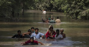 Flood victims wade through a flooded area along a road as they wait for help, in Multan, Punjab province