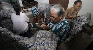 Pekerja menyelesaikan pembuatan batik tulis di Desa Wijirejo, Pandak, Bantul, Yogyakarta