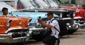Seorang warga mengabadikan mobil antik yang dipamerkan dikawasan lapangan Kantin, Bukittinggi, Sumbar