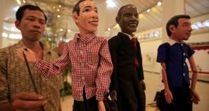 Pengunjung mengamati wayang tokoh politik, Presiden terpilih Joko Widodo (kiri) dan Presiden Amerika Barack Obama (tengah) pada pameran wayang dalam ASEAN – China Collaboration on Tradisional Performing Arts of Puppet Performance 2014 di Taman Budaya Jaw
