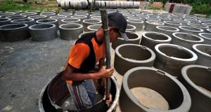Seorang pekerja mencetak buis beton dengan campuran semen dan pasir untuk pembuatan sumur di Kel. Bakung, Maro Sebo, Kab. Muaro Jambi, Jambi.