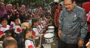 Gubernur Jatim Soekarwo (kanan) disambut sejumlah anak - anak dengan musik drum band saat menghadiri peringatan Hari Anak Nasional, di TSI II Prigen, Pasuruan, Jatim, Sabtu (27/9).