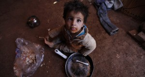 A Syrian refugee child eats inside his family's tent at an informal settlement in Deir al-Ahmar, Bekaa valley