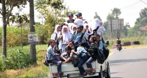 Sejumlah siswa menumpang kendaraan bak terbuka usai pulang sekolah ketika melintas Desa Tuwel, Kabupaten Tegal,