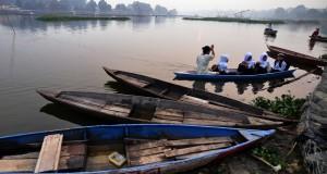 Pelajar menyeberang menggunakan perahu tradisional untuk berangkat ke sekolah  dari Desa Danau Sipin menuju Desa Telanai di Danau Sipin, Jambi