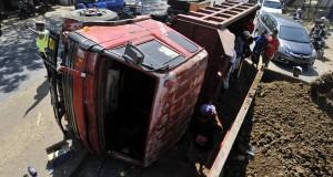 Sejumlah warga berusaha mengevakuasi mobil truk pengangkut timbunan terguling di Jalan Aroe Pala Makassar, Sulsel, Senin (29/9)
