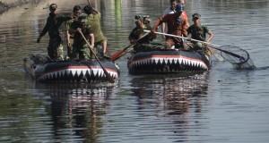 Prajurit TNI mengangkat sampah di sekitar kanal pada kegiatan karya Bhakti TNI, Makassar