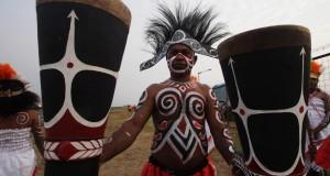 Sejumlah warga aseli Papua memainkan alat musik Tifa di Bandara Mopah, Merauke, Papua