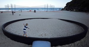 """A boy runs along the rim of a giant frying pan sculpture by Andrew Hankin titled 'We're frying out here' as part of the """"Sculpture by the Sea"""" exhibition at Sydney's Tamarama Beach"""