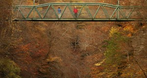 People stop on a bridge over the River Garry to view the autumn scene near Killiecrankie in Scotland