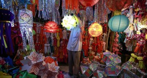 A vendor hangs a lantern for sale at a Diwali market in Mumbai