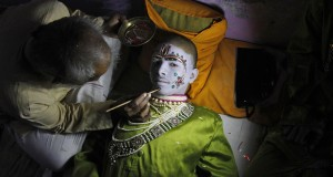 Kumar gets makeup applied before performing the role of Rama in a religious play ahead of Dussehra in Allahabad
