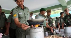 Prajurit TNI memasukan batang kayu sebagai bahan bakar, kedalam kompor Babinsa Rakyat, di Lapangan Benteng, Medan, Sumut, Rabu (1/10).