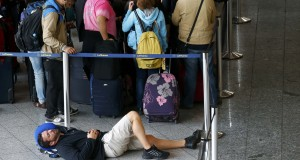 A passenger sleeps on the floor as others queue for the Lufthansa check-in counters at Frankfurt airport